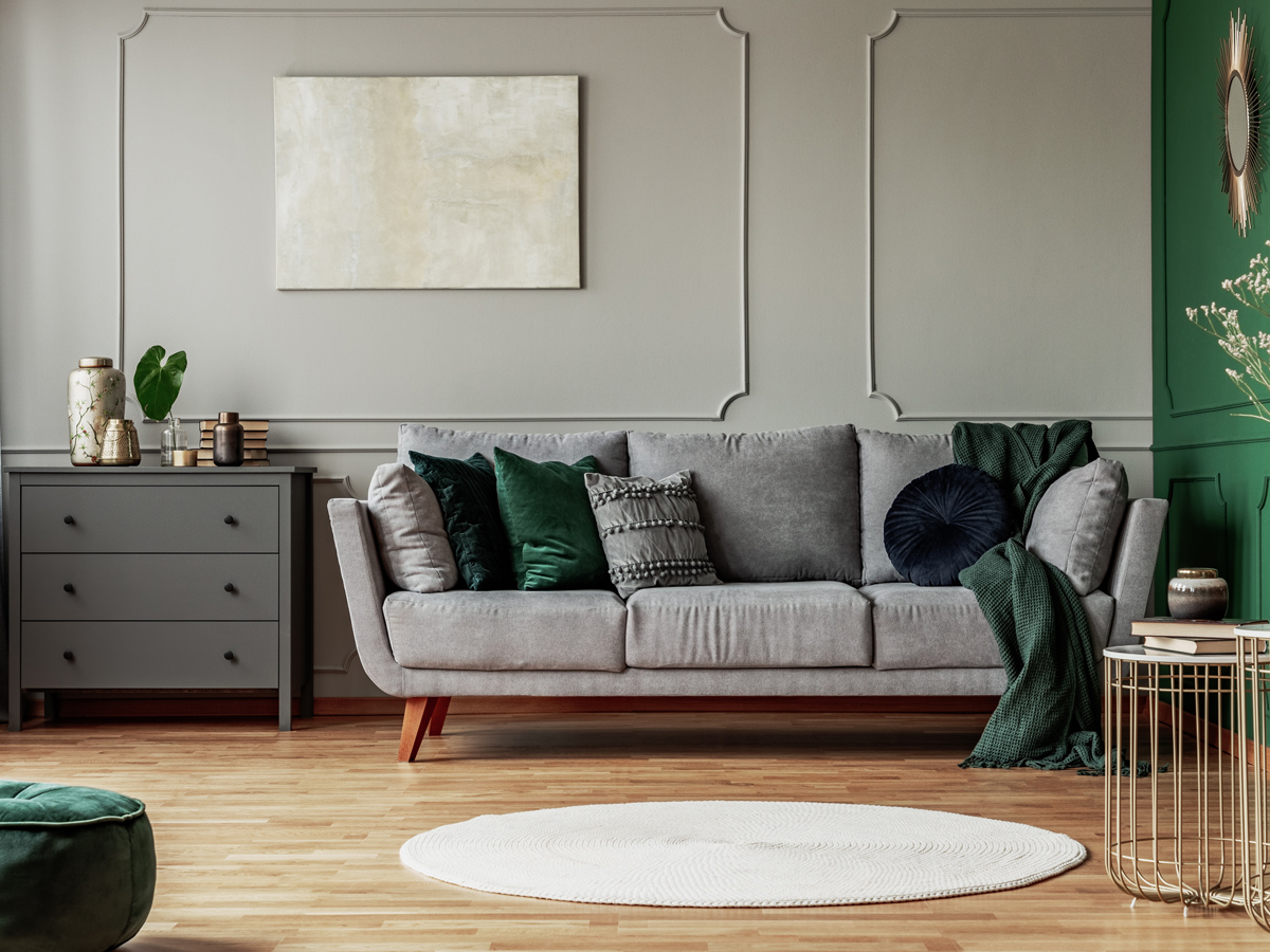 Additions and Interiors Stylish emerald green and grey living room interior design with abstract painting on the wall