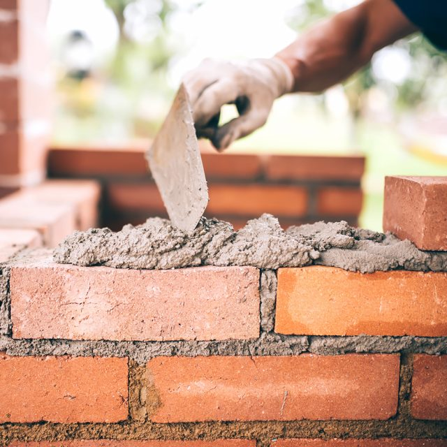 Masonry Spain Costa Blanca i-rebuild industrial Construction bricklayer worker building walls with bricks, mortar and putty knife